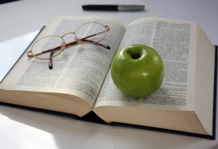 Apple and reading glasses resting on a book